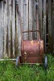 Una carretilla vieja y oxidada en fondo de madera Imagenes de archivo
