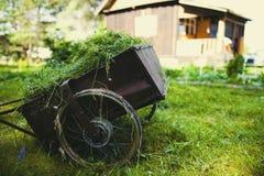 Una carriola con erba falciata contro il contesto di una casa del villaggio fotografie stock