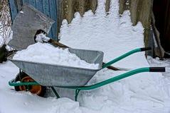 Una carriola del ferro con neve e una grande pala nell'iarda di inverno fotografia stock