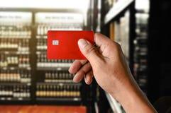 Una carta di credito della tenuta della mano sul fondo del deposito del supermercato del vino Immagini Stock