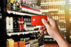 Una carta di credito della tenuta della mano sul fondo del deposito del supermercato del vino Fotografie Stock Libere da Diritti