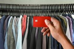 Una carta di credito della tenuta della mano sulle magliette tormenta in negozio Immagini Stock Libere da Diritti