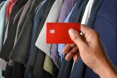 Una carta di credito della tenuta della mano sulle magliette tormenta in negozio Fotografia Stock Libera da Diritti
