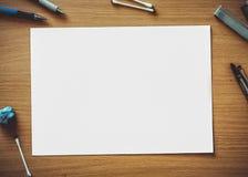 Una carta rectangular puesta en una tabla de madera de color marrón y un caramelo de la piruleta, las plumas y otros objetos se p fotos de archivo libres de regalías