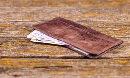Una cartera, el dinero y otros artículos están en la tabla de viejos tableros