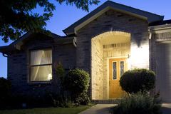 Una casa agradable del ladrillo en noche amistosa de la comunidad Fotos de archivo libres de regalías
