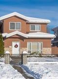Una casa americana típica en invierno Casa nevada imagen de archivo