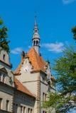 Una casa antica con bella architettura con i fronti di orologio da due lati di alta torretta sul tetto con un aguzzo Fotografia Stock Libera da Diritti