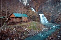 Una casa cerca de la cascada Imagen de archivo libre de regalías