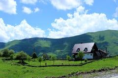Una casa con il tetto marrone e territorio incluso con gli alberi da frutto nelle montagne fotografia stock libera da diritti