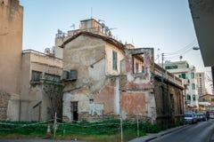 Una casa con las paredes quebradas y el exterior riegan los barriles para el abastecimiento de agua en Nicosia Imagen de archivo libre de regalías