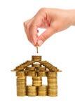 Una casa costruita delle monete isolate Immagini Stock