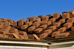 Una casa in costruzione con le pile di assicelle delle mattonelle sul tetto Fotografia Stock