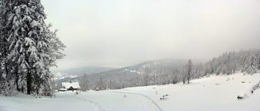 Una casa cubierta con nieve entre muchas montañas fotografía de archivo