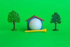 Una casa da una palla da golf circondata dagli alberi e dalla pianta Immagini Stock