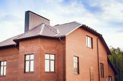 Una casa de campo grande hecha de ladrillo rojo con un tejado tejado El concepto del diseño de una casa de campo moderna imagenes de archivo