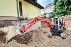 Una casa de la familia se está reconstruyendo con la ayuda de un excavador Foto de archivo libre de regalías