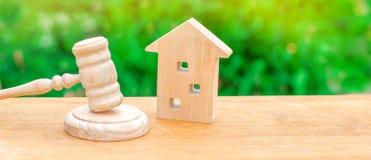 Una casa de madera miniatura y un martillo del juez Comprar/venta de la subasta una casa Desahucio e incautación forzados clarifi fotos de archivo libres de regalías