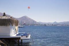 Una casa de planta baja acogedora en la costa y un ala flexible del vuelo contra Foto de archivo libre de regalías