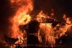 Una casa de un piso de madera grande está quemando con una llama brillante fotos de archivo