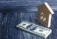 Una casa di legno sta accanto ad una pila di banconote di dolore Il co Fotografie Stock Libere da Diritti