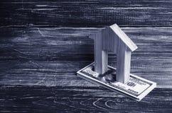 Una casa di legno sta su una pila di banconote di dolore Fotografie Stock Libere da Diritti