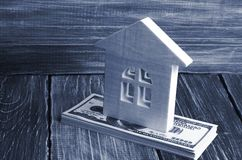 Una casa di legno sta su una pila di banconote di dolore Il concetto di acquisto e di vendita del immovability, affitto degli app Fotografia Stock