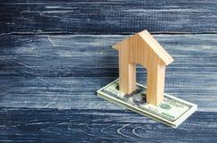 Una casa di legno sta su una pila di banconote di dolore Il concetto di acquisto e di vendita del immovability, affitto degli app Immagine Stock