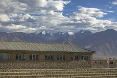 Una casa di pietra con i punti su un fondo delle montagne nevose fotografie stock