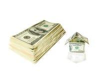 Una casa fatta dalle fatture del dollaro e da molti dollari Fotografie Stock Libere da Diritti