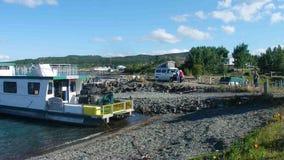 Una casa flotante que es lanzada para la estación en el lago del atlin metrajes