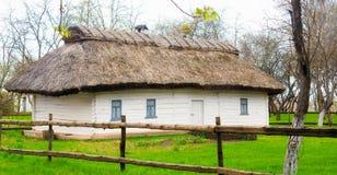 Una casa histórica antigua en el pueblo ucraniano Un edificio blanco con los obturadores amarillos en las ventanas y un tejado Fotografía de archivo libre de regalías