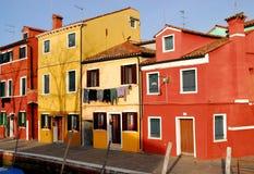Una casa rosso scuro ed altra colorata nell'area Italia di Burano Venezia Immagini Stock Libere da Diritti