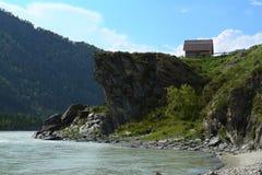 Una casa sulla riva di un fiume della montagna Fotografie Stock Libere da Diritti