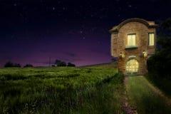 Una casa vieja del vintage al lado del campo de trigo con la luz caliente dentro en la noche Foto de archivo libre de regalías