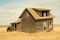 Una casa vieja que soporta algunos neumáticos del tractor Fotografía de archivo