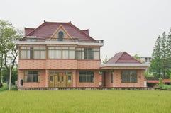 Una casa y una tierra de cultivo chinas del pueblo foto de archivo