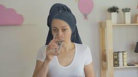 Una casalinga femminile con un asciugamano legato intorno alle sue pillole cape dei sorsi con acqua da un vetro video d archivio