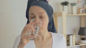 Una casalinga femminile con un asciugamano legato intorno alle sue pillole cape dei sorsi con acqua da un vetro stock footage