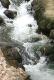 Una cascada está en montañas Fotografía de archivo