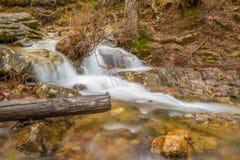 Una cascada fluye después de una lluvia en un barranco ocultado en una montaña foto de archivo libre de regalías