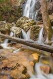 Una cascada fluye después de una lluvia en un barranco ocultado en una montaña imagenes de archivo
