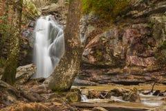 Una cascada fluye después de una lluvia en un barranco ocultado en una montaña imagen de archivo