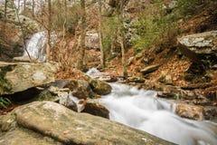 Una cascada fluye después de una lluvia en un barranco ocultado en una montaña foto de archivo