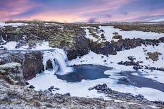 Una cascada helada durante salida del sol en Islandia Imagen de archivo