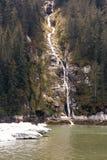 Una cascada que viene abajo el lado de un acantilado en los wi del fondo Foto de archivo libre de regalías