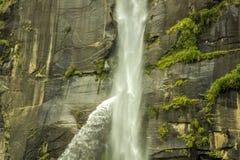 Una cascata abbandonata su una roccia con muschio fotografia stock