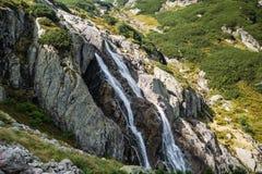 Una cascata gigante nelle montagne fotografie stock libere da diritti