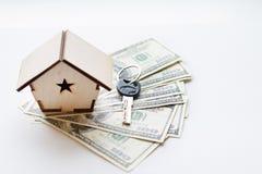 Una casetta si trova su un fan di cento banconote in dollari Le chiavi alla casa acquistata Copia riduttrice della casa fotografie stock
