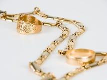 Una catena dorata e due anelli immagine stock libera da diritti